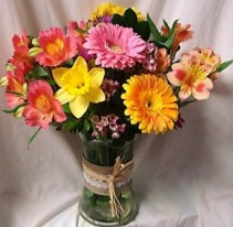 TOUCH OF SPRING...CUTE RAFFIA RIBBON DETAIL ON  vase with lillies gerbera daisies and yellow daisies arranged in a vase with spring  filler.