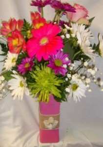 Cute colored vase with a burlap flower detail and spring flowers!