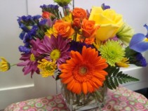 Bright mixture of flowers arranged in a clear cube vase.