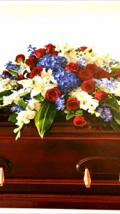 PASSIONATE GRACE Half Casket Spray of seasonal Reds, whites and Blues. Roses, delphinium,  hydrangea and more.