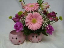 Pink Happy Face ceramic container with shades of  pink flowers...roses, gerbera daisies, carnations etc.