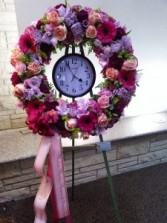 Multi color wreath adorned with clock to mark time of passing