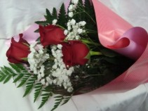 3 Red Roses wrapped in nice paper with baby's Breath and greens with watertubes! Can call to pick up or have it delivered.